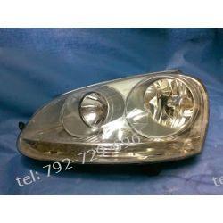 GOLF V lewa lampa przód szara + silniczek, HELLA, uchwyt od strony grilla reperowany